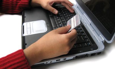 hand-holding-credit-card-near-laptop